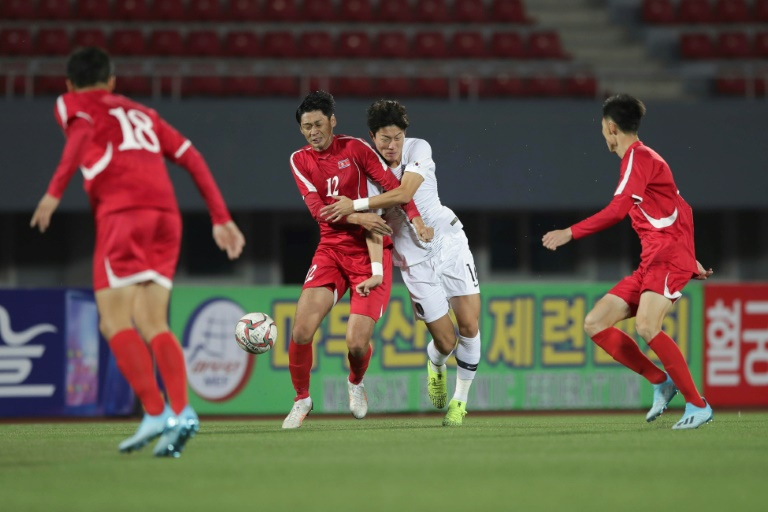 South Korea's Hwang Ui-jo and North Korea's Ri Yong Jik fight for the ball during the World Cup 2022 Qualifying match in Pyongyang