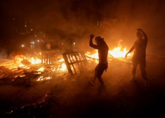 Lebanese demonstrators in Beirut burn wood and debris during a protest against new taxes