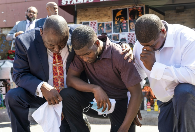 Quincy Mason Floyd (C), son of George Floyd, kneels at the site where his father died in Minneapolis